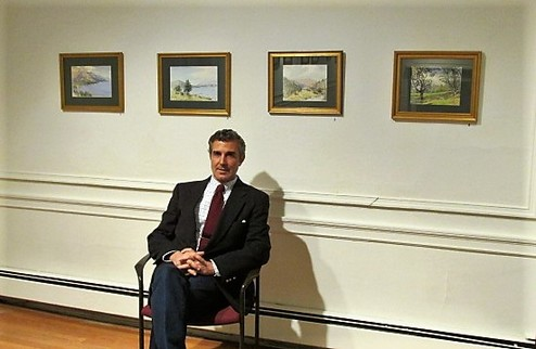 Picture of the artist next to some framed artwork.